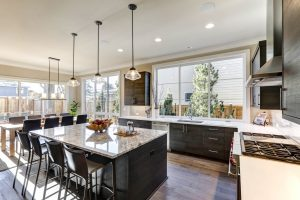 Modern gray kitchen features dark gray flat front cabinets paired with white quartz countertops and a glossy gray linear tile backsplash.